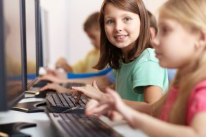 Happy children at school working with computers, become a teacher's aide with Phillips Institute